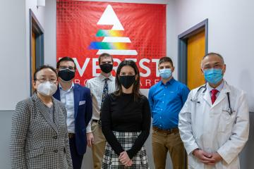 6 people stand in front of a red banner that says Everest Urgent Care