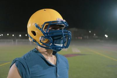 A football players wears the achieve mask under his helmet