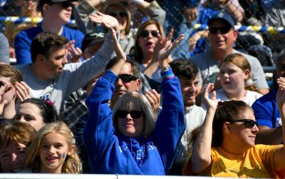 alumni, students, and families cheer in football stands at homecoming