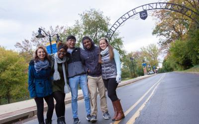 students post in front of archway that reads widener university
