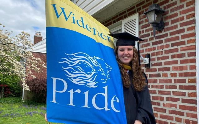 widener graduate in cap and gown with widener pride flag